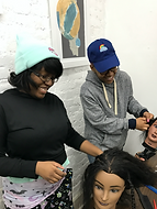 A teacher and male student working on mannequin head's hair
