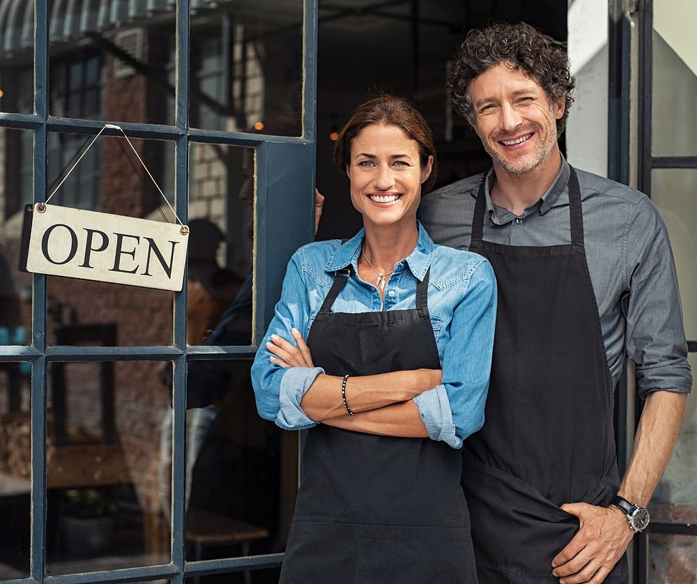 two people infront of their open business sign