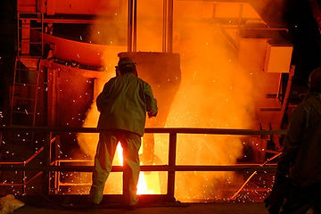 person looking over railing at a foundry