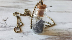 necklace with coal in bottle