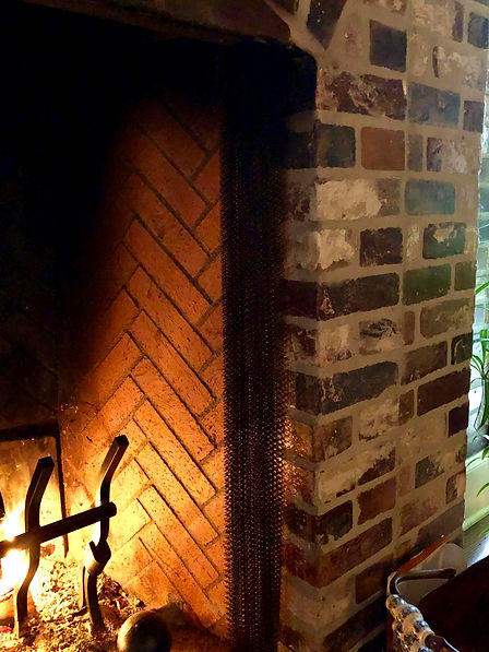 PortStone thin brick fireplace surround.  Corner brick wrapping a corner.  Rose Hill brick color.  Fire in a fireplace.  Mesh fire screen.  Tall andirons. Close-up view of thin brick around a fireplace.