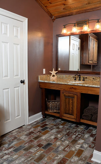 Bathroom with brick floors.  Cypress bathroom cabinets.  Cypress cabinet with a granite countertop.  St. Louis brick floor in a bathroom