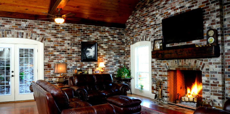 Thin brick on a wall.  Rose Hill brick color.  PortStone thin brick around a fireplace.  Antique pine floors.  Wood beam truss ceiling.  Exposed wood beams.  Cypress mantle.  Brick arch over doors.  Cypress board ceiling.  large room with brick walls. Exposed brick on a wall. DIY thin brick wall.