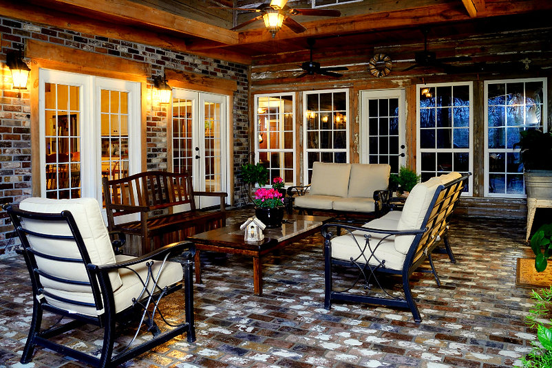 Covered patio with a brick floor.  St. Louis Thin Brick Patio and Walls.  PortStone thin brick for porches and walls. Old recycled wood planks on a porch wall.  Antique brick.  Cypress wood beams. Outdoor living area.