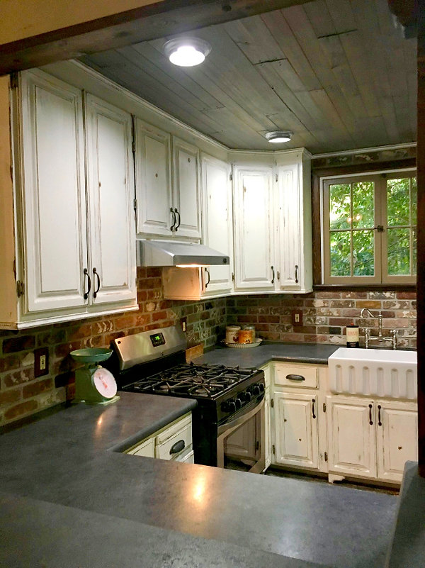 Thin brick on a kitchen wall.  Rose Hill brick color.  Kitchen remodel with brick walls.  Metal ceiling tiles on a bar front.  Old wood look flooring.