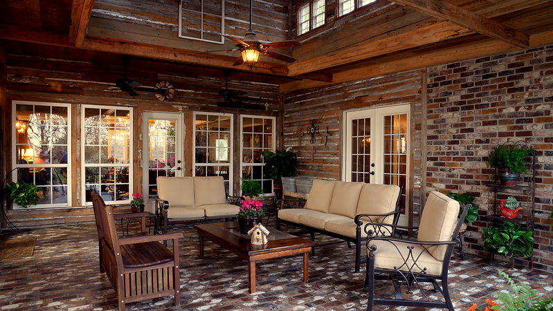 Outdoor living.  Beautiful covered brick patio with old recycled wood plank walls.  St. Louis brick flooring.  Rose Hill thin brick wall.