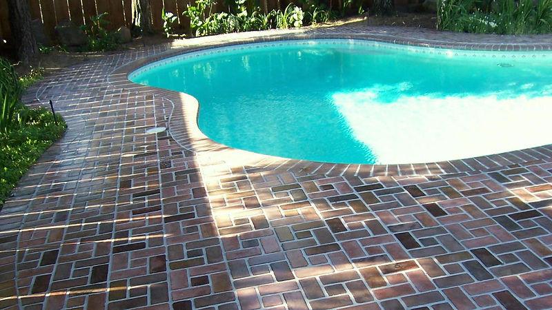 Brick pool deck.  Swimmingpool with a brickpol deck. Thin brick around a pool.  PortStone thin brick.