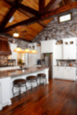Kitchen with brick walls.  Brick backsplash.  thin brick on a back splash. Cypress vent hood. granite countertops. long kitchen island. Thin brick on a wall.  Rose Hill brick color.  PortStone thin brick in a kitchen.  Antique pine floors.  Wood beam truss ceiling.  Exposed wood beams.  Cypress mantle.  Brick arch over doors.  Cypress board ceiling.  large room with brick walls. Exposed brick on a wall. DIY thin brick wall.