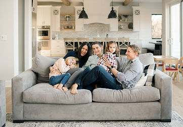 family_cuddles_on_the_couch_of_their_new