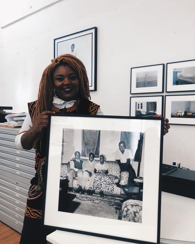 Diane Audrey Ngako, grande figure de l'art cpntemporain africain; pose avec une photographie de James Barnor, issue de sa collection privée