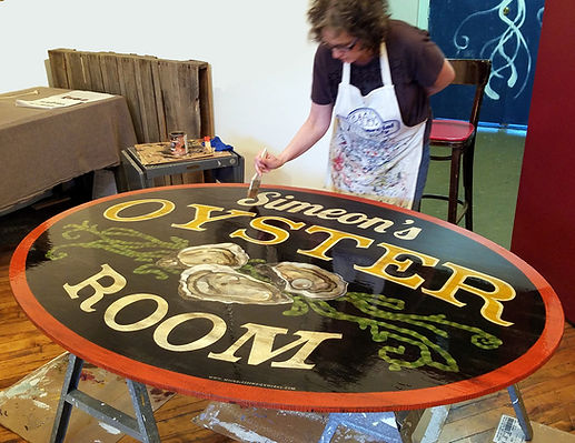 Beth Brown varnishing a sign copy.jpg