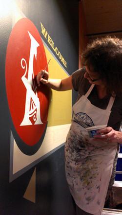 Beth Brown painting a mural