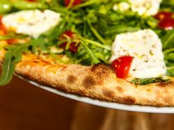 une_pizza_légère_et_croustillante_garnie_de_produits_italiens_et_frais