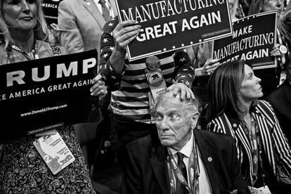 """Delegates from California holding up signs stating """"Make manufacturing great again"""". Trump wants companies and business owners to have products produced in the United States and not outside the country. This is inconsistent with Trump's own products: Shirts, ties and hats made in China, Bangladesh, Honduras and Vietnam"""