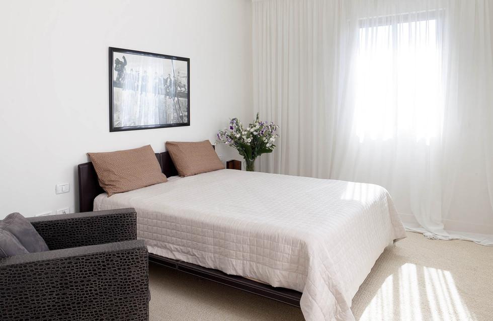 חדר אורחים בעיצוב מינמלי בהיר, המיטה והספה מעור, חומרים טבעיים העומדים מול הרכות של וילון הפשתן