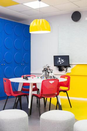 שולחן עגול המאפשר מפגשים לצורך תכנון קבוצתי. ברקע- ארון הלגו הכחול