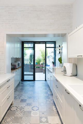 מעבר לחיפוי הבריקים, הרחבת המטבח על חשבון הגינה המקורה. דלת יציאה בלגית מקשרתבין המטבח אל החצר