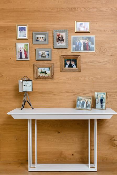 הקיר חופה בפרקט עץ וממסגר את תמונות המשפחה, מתחת לקיר מוצבת הקונסולה הנפתחת עד גודל של 3.4 מטר.