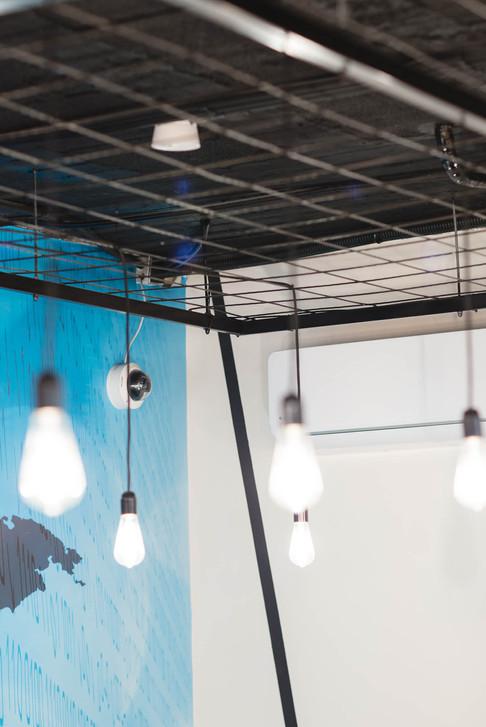 רשת ברזל שחורה על תקרת בטון, עליה נפרשים כבלי תקשורת וחשמל