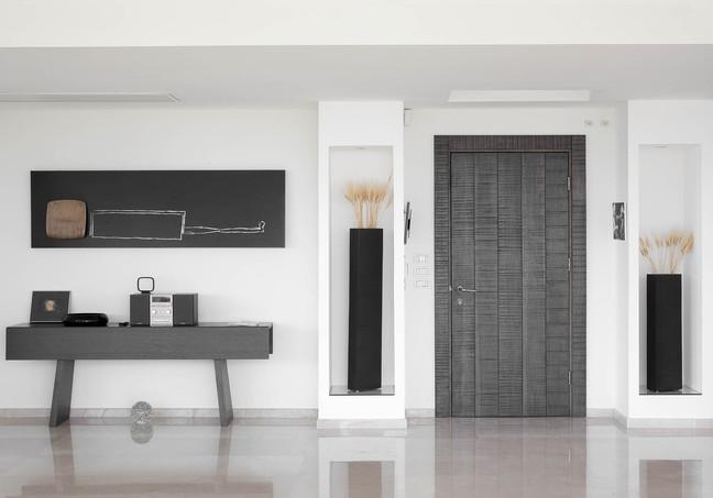 דלת הכניסה לדירה עשויה עץ טבעי גס, המשתלב עם השימוש בחיטה ובתמונה הסמוכה המשלבת עץ טבעי ועם קונזולת הכניסה לבית