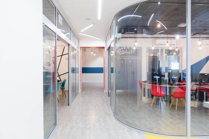 חלל גדול המחולק באמצעות מחיצות זכוכית מעוגלות לחדרי למידה