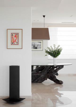 שולחן אוכל מינימליסטי מציץ מאחורי העמוד העיקרי התומך את הבית. שימוש בעמוד כאלמנט עיצובי