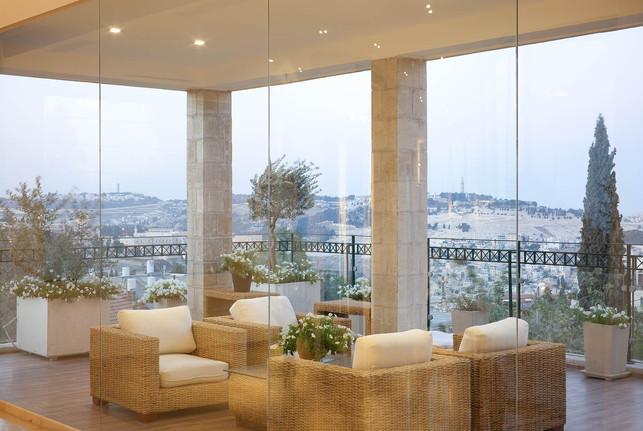 מבט מן הסלון אל מרפסת מקורה, שנתחמה בקירות מסך מזכוכית ומכניסה את החוץ פנימה ואת הפנים החוצה