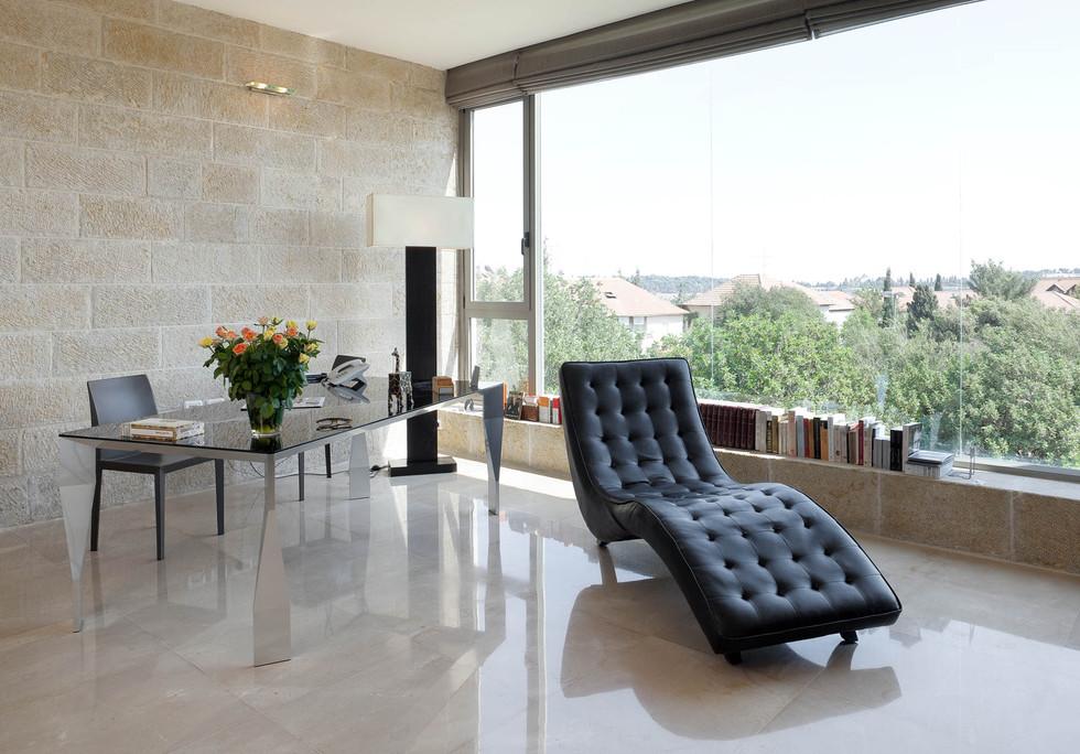 מרפסת שנסגרה והפכה לחדר עבודה, קיים מתח בין קירות האבן הטבעיים לקירות הזכוכית השיש המודרני ועיצוב חדר העבודה