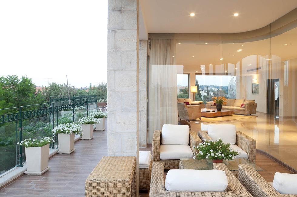 מבט מן המרפסת אל פנים הבית, עיצוב מינמליסטי נקי ומאפשר שקיפות מלאה של הפנים החוצה והחוצה פנימה