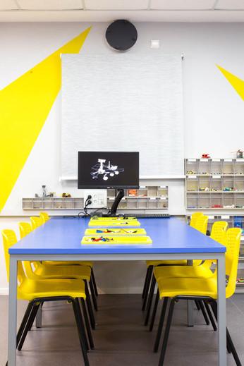 תאי אחסון לגו משולבים בשולחן העבודה. מסך תלוי על הקיר, על מנת להשאיר את משטח העבודה פנוי