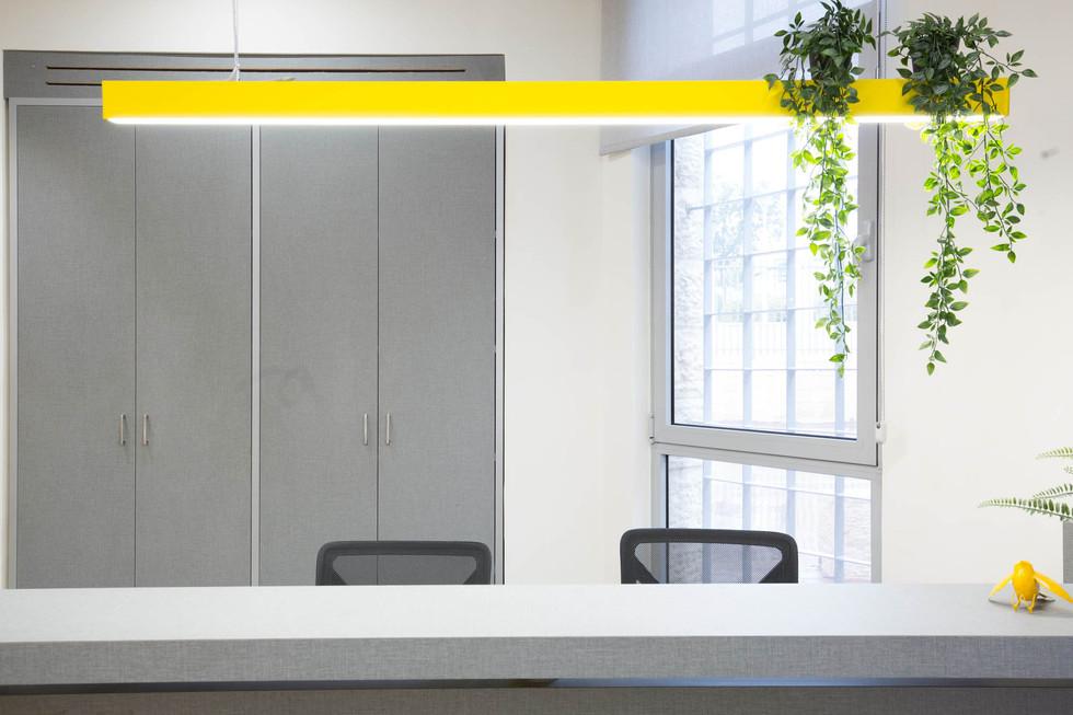 פרופיל תאורה תלוי בצבע צהוב מדגיש את שולחן הקבלה, ארונות אחסון מאחורי הדלפק