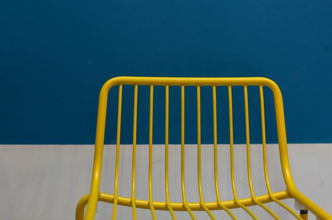כסא ברזל צהוב על רקע קיר כחול. משחק של צבעים וחומרים