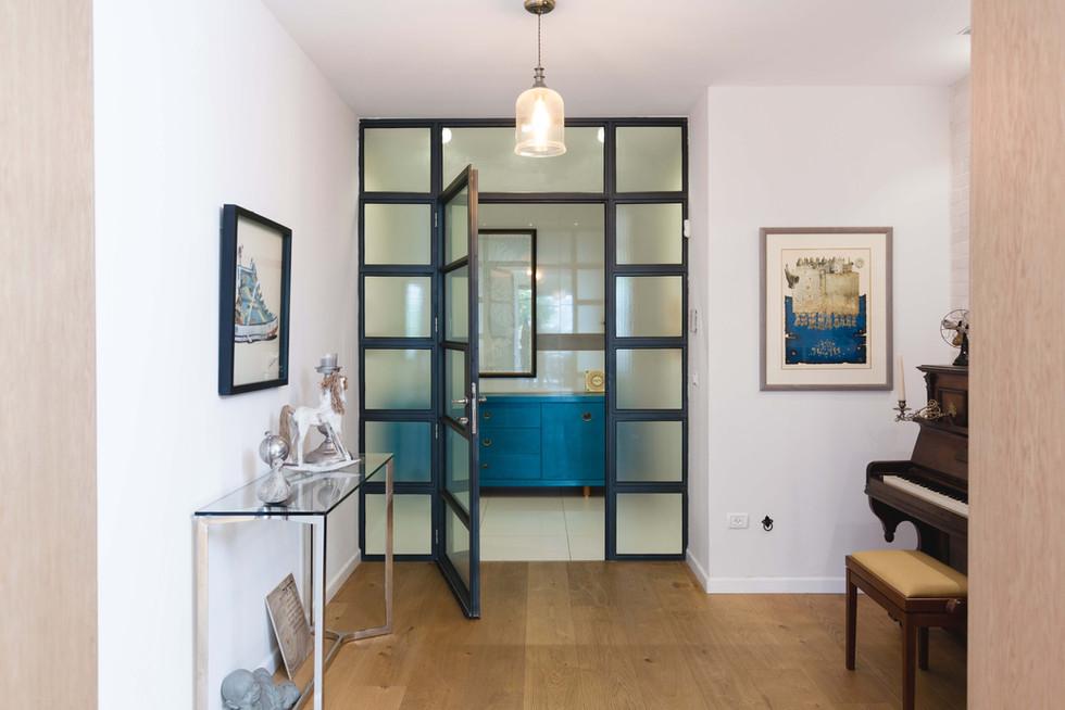 דלת מפרופיל אלומיניום בלגי של קליל כדלת כניסה לדירה בבניין אינה בחירה קונבציונאלית, אך מיד בכניסה מרגישים שזו אינה דירת קבלן רגילה
