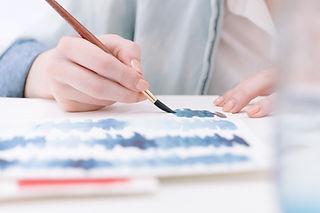 Uma aluna realizando testes de cor utilizando a pintura a guache