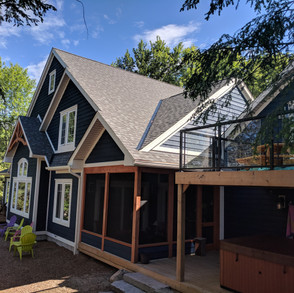 Back of large blue cottage with screened in porch