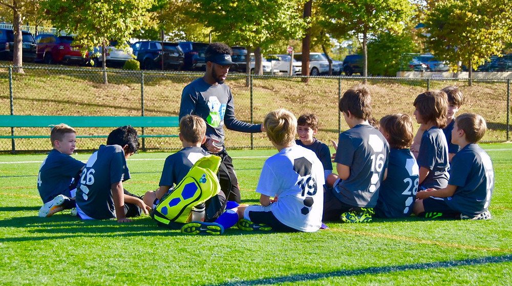 Coach Seisay going over the game plan with his team.