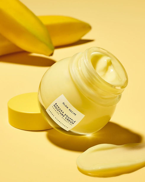 Photo of banana moisturizer from glow recipe, the jar is open and tilted onto the lid, showing the smooth light yellow cream that looks like custard. the surface its on is yellow and there are bananas in the background.