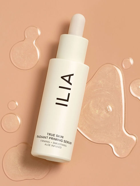 Photo of Ilia's priming serum. An off-white matter opaque plastic dropper bottle with minimalist sans serif typography. It's on a beige surface with drops of the serum on it, the serum has a light shimmer to it.