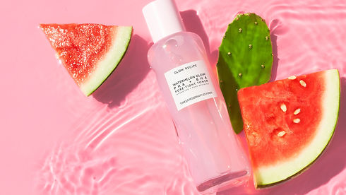 Photo of watermelon glow toner from glow recipe. It's shot from above, the tall bottle is made out of clear glass but has an uneven surface. the background is pink and coved with a thin layer of water. There are pieces of watermelon beside the bottle.