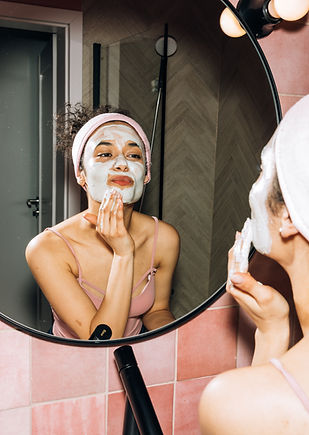 young woman looking at herself in the mirror while putting on a face mask