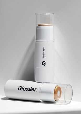 Haloscope Dew Effect Highlighter from the brand Glossier, it's white with black sans serif text.