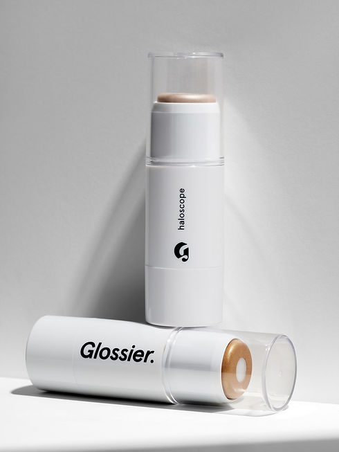 Photo of highlighter from glossier. It's a stick highlighter in a white plastic tube with the name of the brand and product in black text.