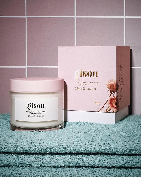 Photo of gisou's hair mask with the secondary packaging, a pink and white paper box, beside it.
