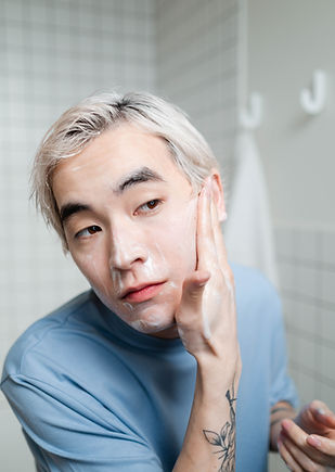 Photo of young asian man with white hair cleansing his face