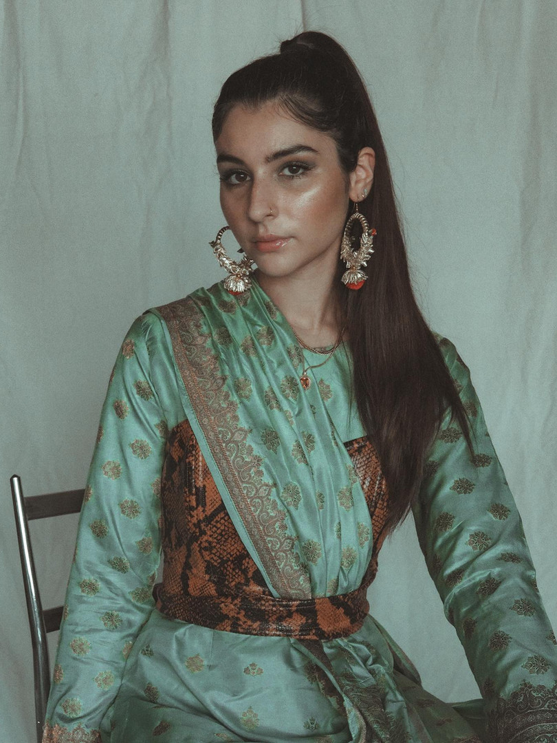 This material banarasi. It's a silk fabric originating from Uttar Pradesh in India but also worn in Pakistan, where my mom purchased it and got it sewn into shalwar kameez instead of a sari. I styled it with my sisters chucks, my other sisters mehndi earrings & a pleather snake skin bodice.