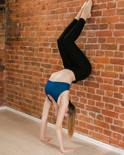 девушка стоит на руках у стены