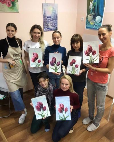 девушки демонстрируют свои рисунки после урока маляной живописи
