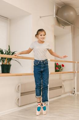 девочка учится стоять на пуантах