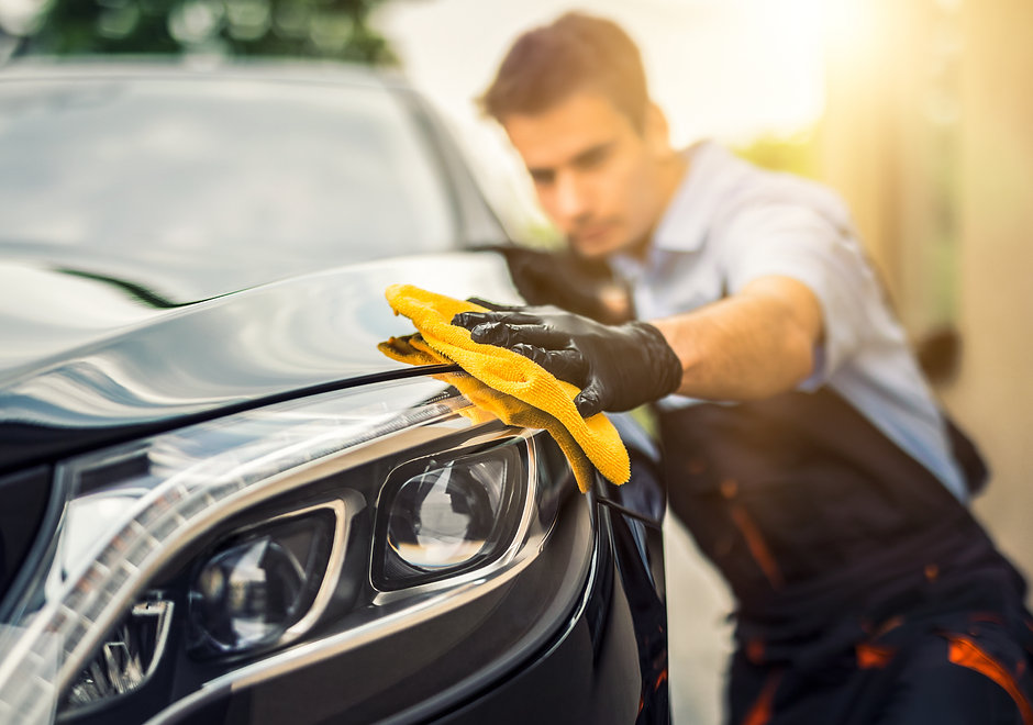 Car detailing - the man holds the microf