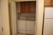 Laundry area with storage cabinets off kitchen